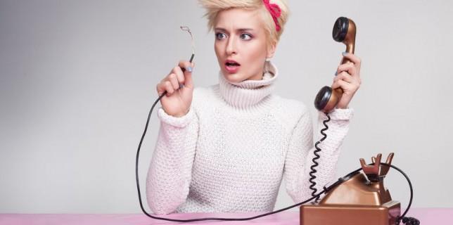בחורה מפותעת אוחזת בכבל טלפון מנותק